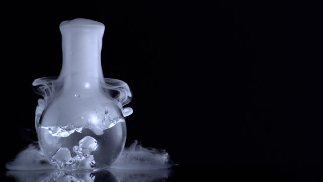 vidéos et rushes de smoke from dry ice and water leaking from a flask on black background - science