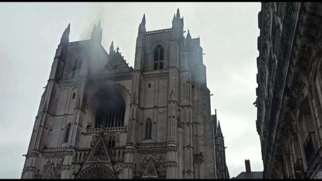 smoke is rising as dozens of firefighters are battling a fire inside nantes cathedral, in western france. the fire is now contained - nantes stock videos & royalty-free footage