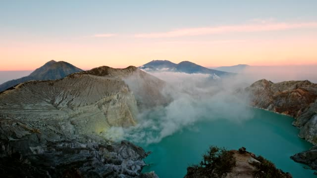 smoke on crater with turquoise lake in valley at morning. kawah ijen, indonesia - indonesia landmark stock videos & royalty-free footage