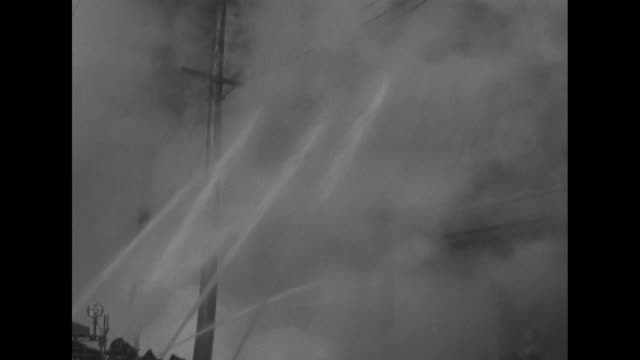 smoke pouring from building on fire, firemen standing in front of building, fireman standing on fire truck next to them, ladder extending up from... - fire hose stock videos & royalty-free footage