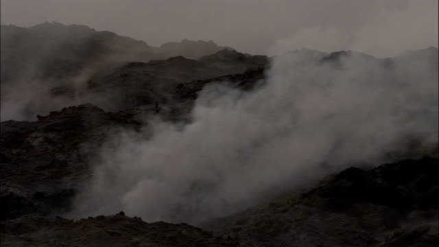 Smoke pours from volcanic ground fissures. Available in HD.