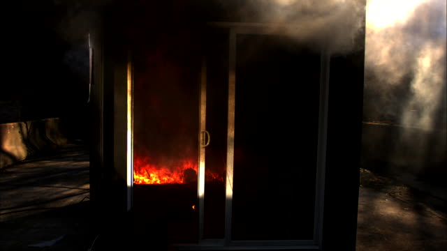 smoke pours out of a enclosed room as a fire burns within it at night. - sauna stock videos & royalty-free footage