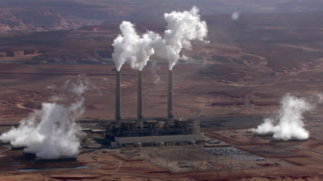 smoke pours out of smokestacks at the navajo generating station's coal-fired power plant in arizona. - coal fired power station stock videos and b-roll footage