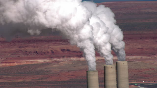 smoke pours out of smokestacks at the navajo generating station's coal-fired power plant in arizona. - smog video stock e b–roll