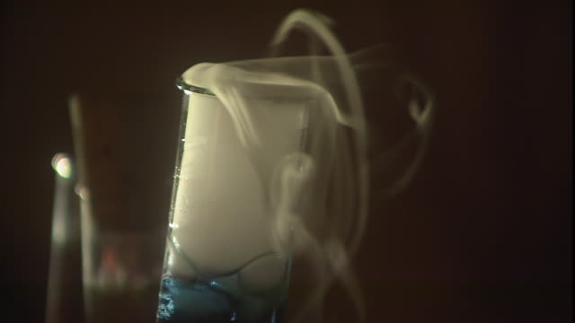 smoke pours out of the top of a beaker filled with blue, boiling liquid. - laboratory equipment stock videos & royalty-free footage