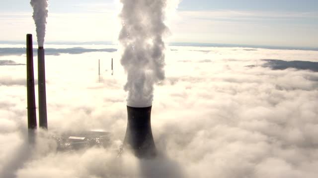 vídeos de stock e filmes b-roll de smoke rises above a fog bank at a coal-fired power plant. - carvão