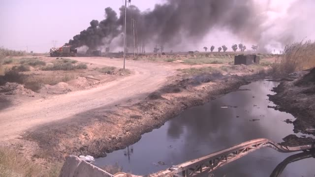 smoke rises after a fire breaks out as daesh terrorists steal crude oil to make smuggled fuel petroleum pipelines of riyadh town of havice district... - ölindustrie stock-videos und b-roll-filmmaterial
