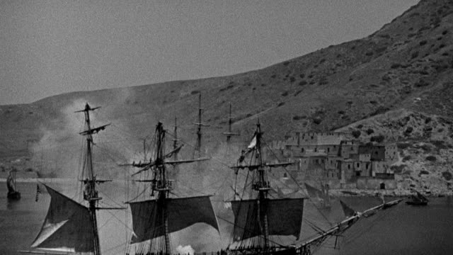 smoke rises as the uss constitution fires a broadside toward a pirate ship and a coastal fort in tripoli harbor. - warship stock videos & royalty-free footage
