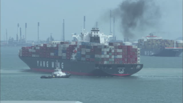 Smoke rises from a container ship as a tugboat guides it in a harbor channel.