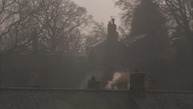 Smoke rises from a rooftop chimney in Northumberland England. Available in HD.
