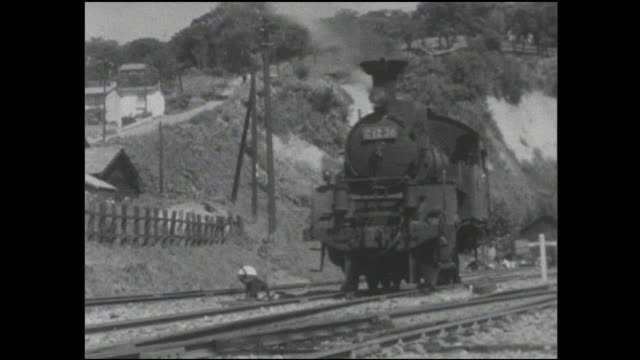 stockvideo's en b-roll-footage met smoke rises from a steam locomotive as it moves on a mainline track. - locomotief
