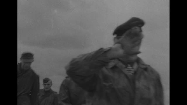 smoke rises from battlefield / german officer sits in jeep and is driven away german prisoners walk along path strewn with rubble officer possibly... - deutsches militär stock-videos und b-roll-filmmaterial