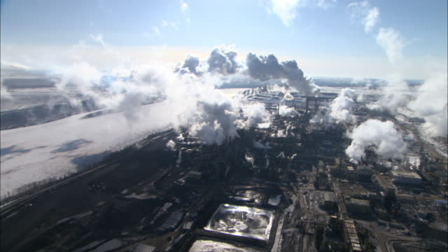 vídeos de stock, filmes e b-roll de smoke rises from buildings in an alberta oil sand extraction operation. - alberta