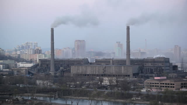 smoke rises from chimneys at a coal fired power plant factory in the city of pyongyang, north korea. - north korea stock videos & royalty-free footage