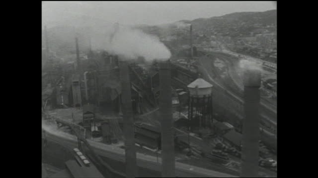 vídeos de stock, filmes e b-roll de smoke rises from chimneys at a kitakyusyu-shi steel mill. - indústria metalúrgica