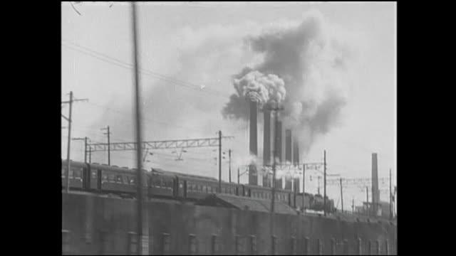 smoke rises from factory smokestacks in kitakyushu, japan. - 機関車点の映像素材/bロール