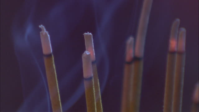 smoke rises from incense sticks as they burn in a buddhist temple. - incense stock videos & royalty-free footage