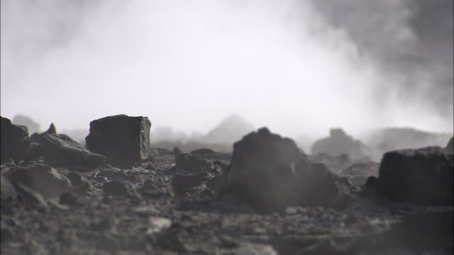 smoke rises from inside the caldera of a volcano. - cenere video stock e b–roll