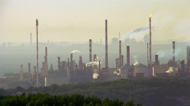 smoke rises from oil refinery smoke stacks. - oil refinery stock videos & royalty-free footage