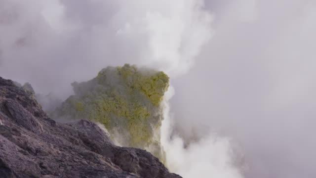 smoke rises from sulphur coated fumaroles on volcano. - sulphur stock videos & royalty-free footage