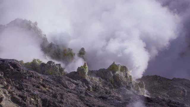 smoke rises from sulphur coated fumaroles on volcano. - 噴気孔点の映像素材/bロール