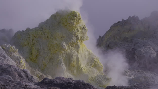 Smoke rises from sulphur coated fumaroles on volcano.