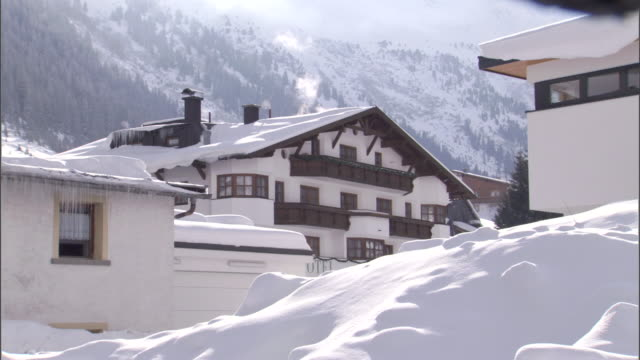 smoke rises from the chimney of a cozy ski chalet. - austria stock videos & royalty-free footage