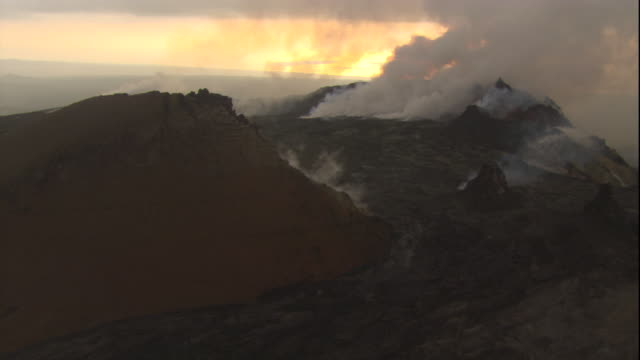 Smoke rises from the summit of a volcano in Hawaii at sunset. Available in HD.
