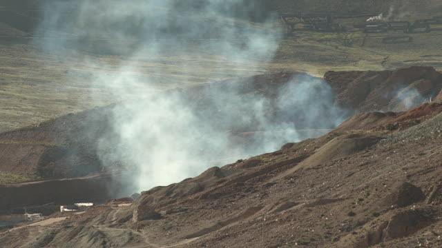 smoke rises slowly from behind a hill in potosi, bolivia. - ボリビア点の映像素材/bロール