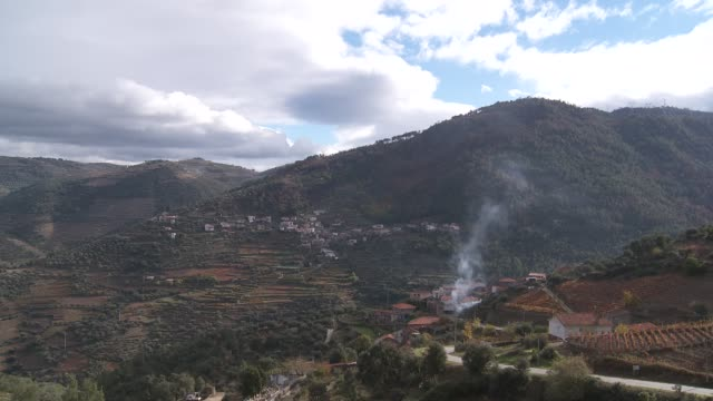 Smoke rises towards terraced vineyards from a small village in the Douro River Valley.