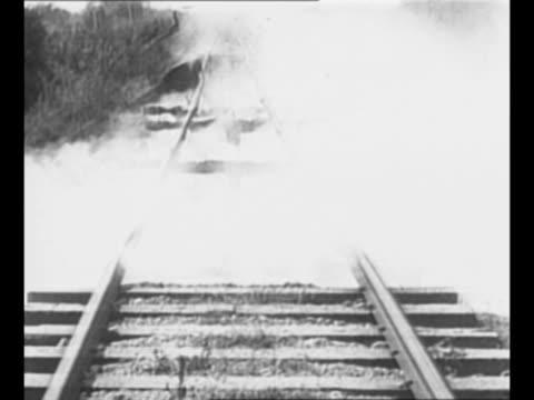 smoke rises underneath destroyed train track / montage derailed train with men standing by / from greatest headlines of the century series / note... - zugunglück stock-videos und b-roll-filmmaterial