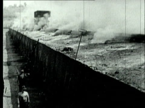 1927 B/W MONTAGE WS Smoke rising from beehive coke ovens at bituminous coal mine and coke works/ WS Workers riding 'larry car' on rails above coke ovens/ Pennsylvania, USA