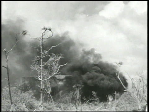 Smoke rising from damaged burning structures thick smoke moving across water VS Wounded 7th Marine Division soldiers being carried on stretcher...