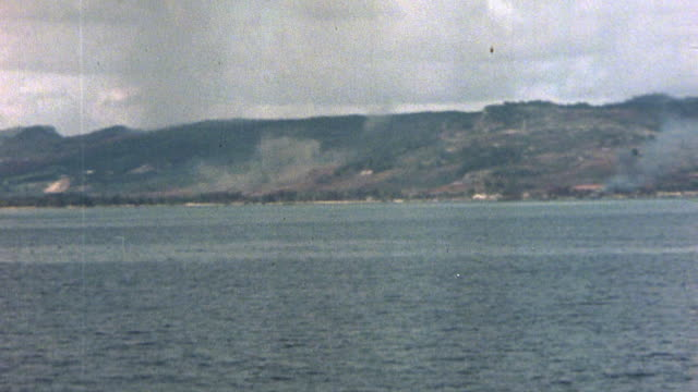 pan smoke rising from garapan shoreline after shelling by uss louisville during the battle of saipan during wwii / mariana islands - mariana islands stock videos and b-roll footage