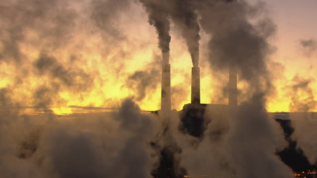 MS AERIAL PAN Smoke rising from Navajo Generating Station against sunrise sky / Arizona, United States
