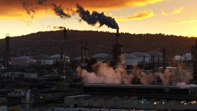 smoke rising from refinery at sunset - aerial - oil industry stock videos & royalty-free footage
