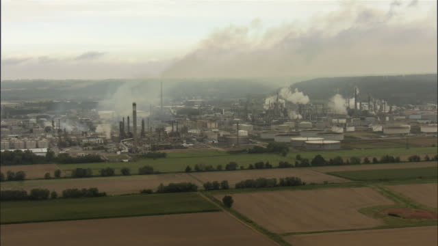 vidéos et rushes de aerial smoke rising from refinery complex surrounded by green fields and bordered by large canal / le treport, haute-normandie, france - industrie du pétrole
