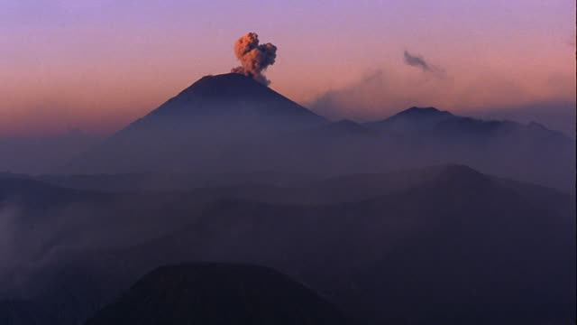 smoke rising from silhouetted mt. semeru volcano with bromo crater in foreground / java, indonesia - bromo crater stock videos & royalty-free footage