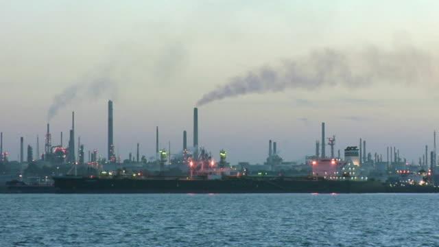 ws smoke rising from smoke stacks at fawley oil refinery on southampton water / fawley, hampshire, england - 工場の煙突点の映像素材/bロール