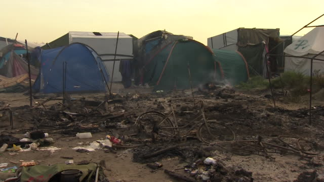 smoke rising from the burned out remains of the 'jungle' migrant camp site - rubble stock videos & royalty-free footage