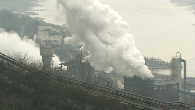 smoke rising from the factory on the riverbank.  wide shot chongqing, sichuan province - luftverschmutzung stock-videos und b-roll-filmmaterial