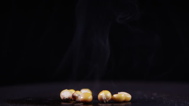 Smoke rising off popcorn seeds rolling on hot plate