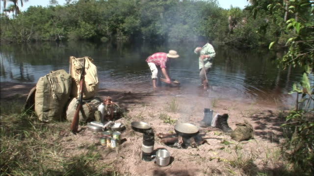 smoke rolls off a pot on a campfire as two men pan for gold on a riverbank. - panning stock videos & royalty-free footage