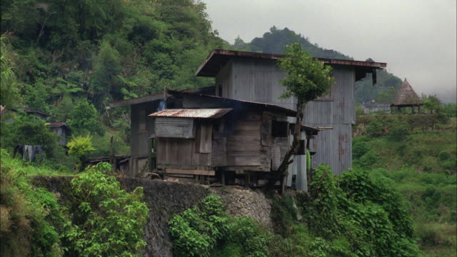 vidéos et rushes de smoke rolls out out of a ramshackle house on a verdant hill. - cahute