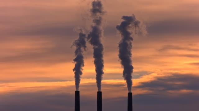 Smoke Stacks against Dramatic Orange Sky