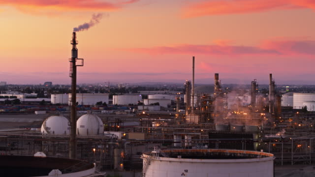 smoke stacks in oil refinery during colorful sunset - drone shot - oil refinery stock videos & royalty-free footage