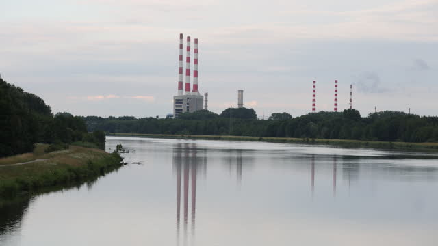 smoke stacks of the gas-fired power plant, operated by uniper se, reflected in calm surface of danube river in irsching, germany on wednesday, july... - water surface stock videos & royalty-free footage