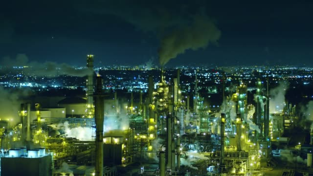 smoke stacks venting in oil refinery at night - aerial - refinery stock videos & royalty-free footage