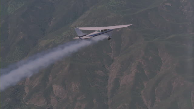 Smoke streams from the engine of a Cessna 172 as it flies toward mountains.