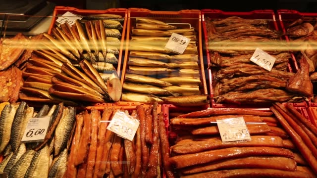 Smoked fish sit on display at a food stall in the central market in Riga Latvia on Saturday Jan 7 Shoppers browse fruit vegetables and caviar at the...